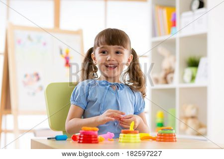 kid girl making by hands in playroom