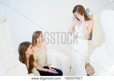 Beautiful bride is under stress because bridesmaids don't approve her dress