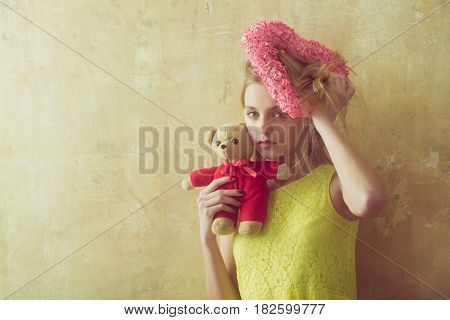 Pretty girl or cute woman with blond hair and adorable face in yellow dress with teddy bear toy and pink wicker heart for valentines day on textured wall background copy space