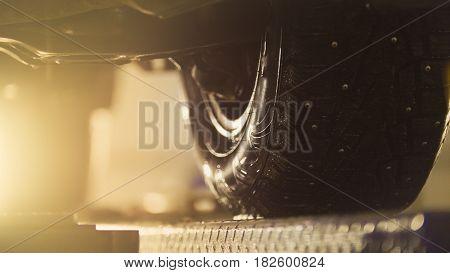 Auto wheel in service, car preparing for professional diagnostics, close up - toned in orange, telephoto