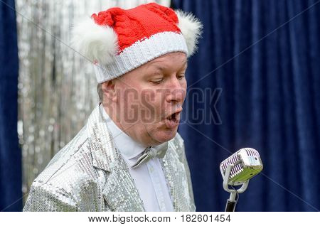 Elderly man wearing a festive red Santa hat singing Christmas songs during a stage performance into a microphone in a close up view