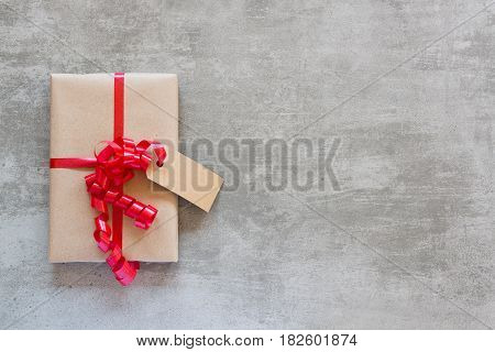 Gift With Red Ribbon And Tag On A Concrete Table