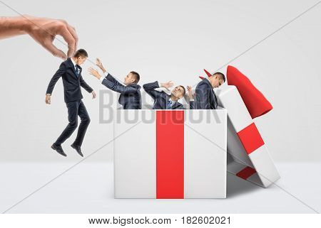 A giant hand holding a tiny businessman near a box full of three other men inside a large gift box. Human resources. Business management. Forced reappointment.