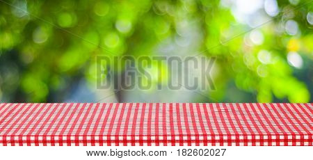 Empty table with red tablecloth over blur green tree and bokeh background for food and product display montage background banner