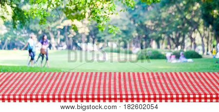 Empty table cover with red tablecloth over blur park with people background for product display montage background banner