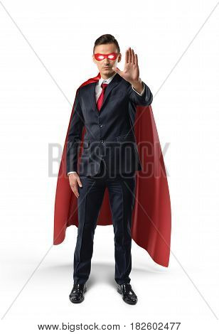 Businessman in a red cape and red eye mask with one hand raised in warning on white background. Business and success. Corporate hero. Superpowers and coaching.
