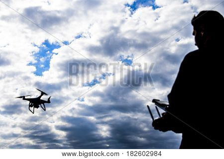 A Man With A Remote Control In His Hands. Controlling The Flight Of The Drone Against The Sky. Phant