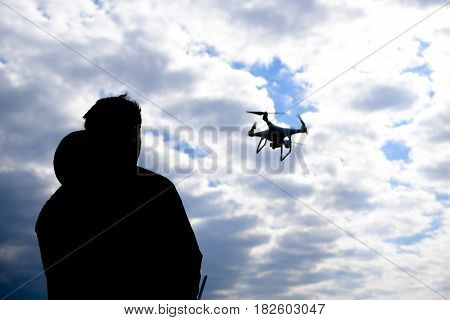 A man with a remote control in his hands. Controlling the flight of the drone against the sky. Phantom