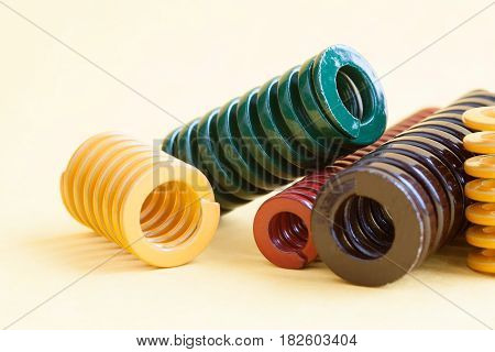Metal coiled springs macro view. Yellow green red brown paint color spirals on yellow background