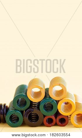 Metal springs with different hardness flexibility sizes. Colorful steel spirals coil wires on yellow background. Copy space.