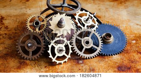 Steampunk still life scene with vintage cog gear wheels on rusty background. Aged clockwork parts macro view. Different cogwheels teeth shapes objects, textured metal surface. Selective focus.