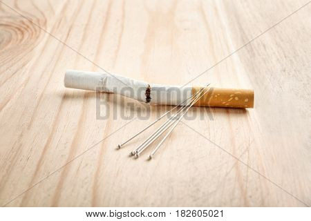 Cigarette with needles on wooden table