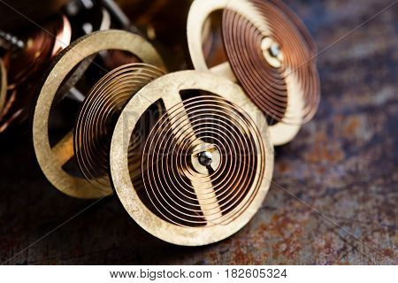 Vintage clockwork wheels with spring mechanism. Brass gears cogs on rusty background, macro view shallow depth of field