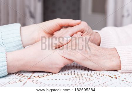 Care is at home of elderly. Space for text. Senior woman with their caregiver at home. Concept of health care for elderly old people, disabled. Elderly woman. Hold hands closeup
