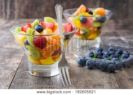 Fruit salad in crystal bowl on wooden table