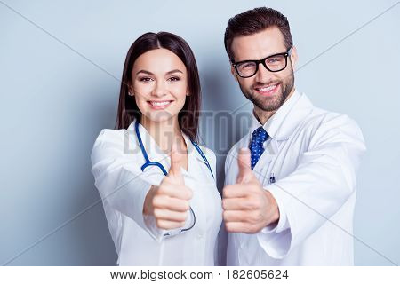 Happy Medic Workers. Portrait Of Two Doctors In White Coats And Glasses Showing Thumb-up Against Whi