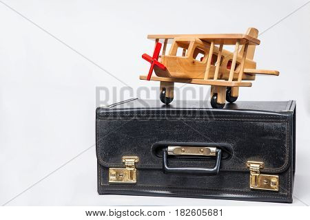 Travel concept : retro style suitcase and biplane on white background