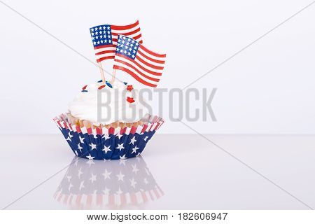 Patriotic 4th of July cupcake with decorative American flags agains white background