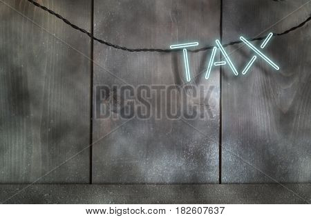 Neon text spelling tax against a wall