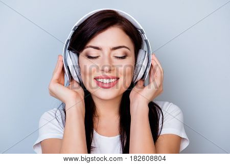 Careless Smiling Woman In Headphones Listening To Her Favourite Song