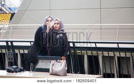LONDON, UK - April 3, 2017: Two muslim women taking a selfie in Canary Wharf, London