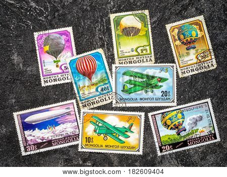 Set of randomly lying postage stamps printed in Mongolia shows hot air balloons dirigible and airplanes series circa 1976-1982 on a dark black cement background.