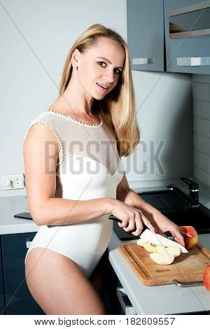 Sexy Beautiful Blond Girl Or Woman Standing In The Kitchen Slicing Apples In Sexy Lingerie And Smili