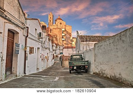 PISTICCI, MATERA, ITALY - MARCH 11: alley in the old town with the typical houses and the ancient mother church in the background. Photo taken on March 11, 2017 in Pisticci, Matera, Basilicata, Italy