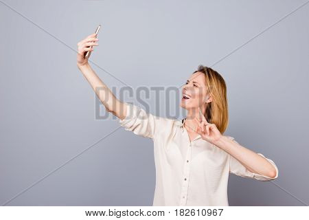 Photo Of Pretty Young Happy Laughing Woman Taking Selfie Using Her Mobilephone, Two-fingers Gesturin