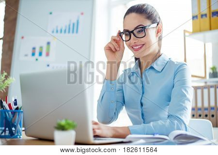 Young Smiling Woman In Formalwear At Work Sitting At The Table And Reading Information From Computer