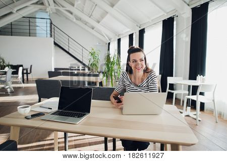 Portrait of an attractive woman sitting at the table with a laptop computer holding phone and looking away searching for inspiration for her book