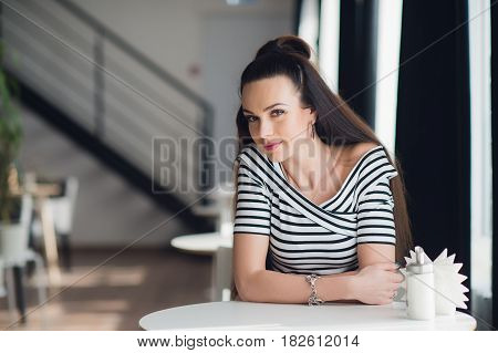 Attractive woman with brunette hair, sexy smiling girl indoors, in a cafe, blurred background. She has lovely smile. Stylish look, make up, light pink lipstick, casual outfit