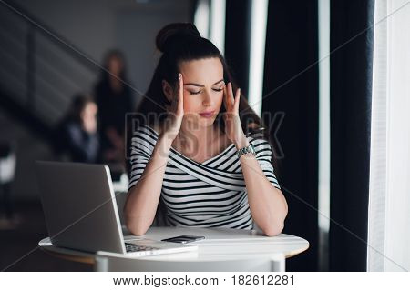 Close up portrait of beautiful woman meditating with closed eyes. Attractive female relaxing from working with a laptop