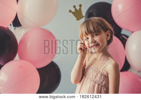 Cute little princess in dress is holding a crown looking at camera and smiling on gray background with colorful balloons