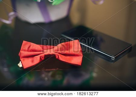 groom's bowtie and the phone are on the table