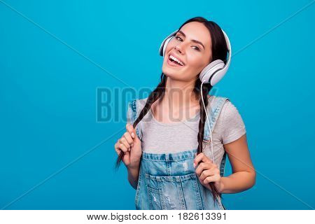Portrait Of Cute Young Girl With Funny Pigtails In Jeans Overalls Listening To Music Against Blue Ba
