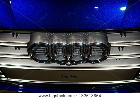 BERLIN - NOVEMBER 09 2016: Showroom. The emblem of compact executive car Audi S5 Sportback 3.0 TFSI quattro tiptronic. Close-up. Produced since 2013 (facelifted).
