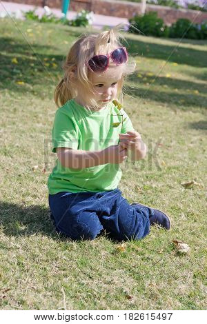 small baby boy or cute child with surprised face and blonde hair in shirt sunglasses and pants sitting on green grass playing with leaves sunny outdoor on natural background