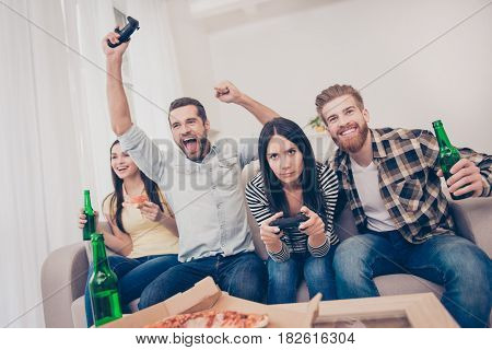 Young People Having Home Party With Video Games, Pizza And Beer. They Show Different Emotions Becaus