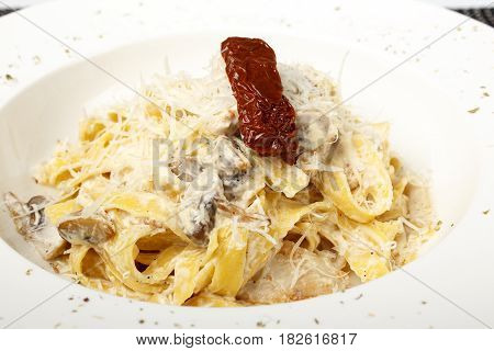 Pasta in white sauce with mushrooms and parmesan cheese isolated on white background