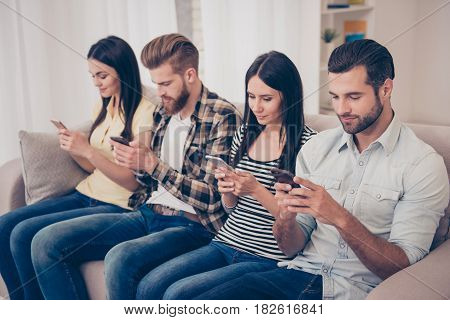 Smiling Concentrated Best Friends Are Sitting On The Sofa At Cozy Home Using Their Phones. They Are