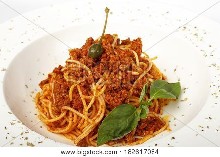 Pasta with meat, tomato sauce, parmesan and vegetables isolated on white background