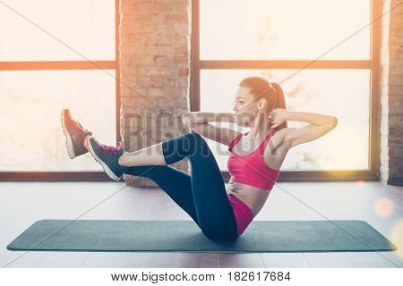 Young Fit And Beautiful Sportswoman Is Exercising On The Mat Indoors. She Is Totally Concentrated On