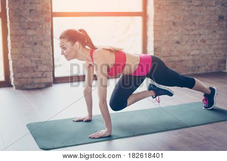 Pretty Young Slim Girl Stretching Her Legs By Doing Exercise. She Is Training On The Green Mat On Th