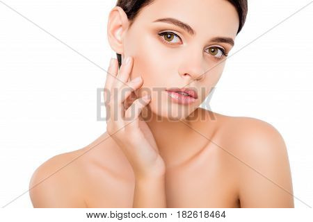 Portrait of young woman touching skin on her cheek