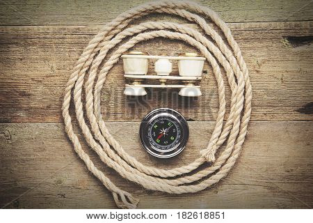 Compass telescope and rope on a wooden table