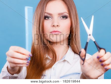Change of look new image. Young girl presents comb and scissors. Female stylist preparing equipment to work cut long straight healthy hair.