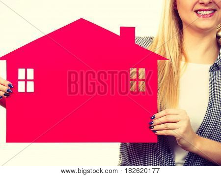 Ownership property real estate concept. Blonde girl holding red paper house symbol. New flat apartment. Toned image