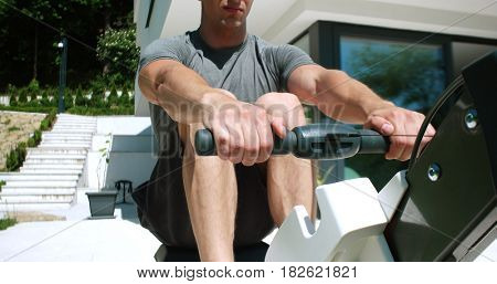 Man Working Out On Row Machine in front of home