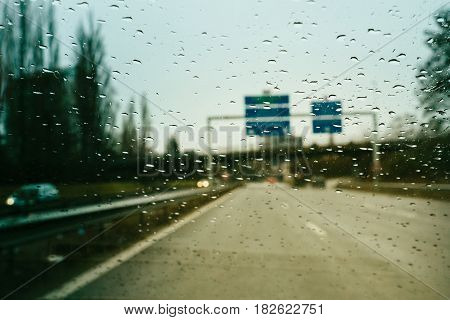 Personal perspective of driver inside car looking at the front view of the highway autobahn on a heavy rain trying to read the defocused highway sign